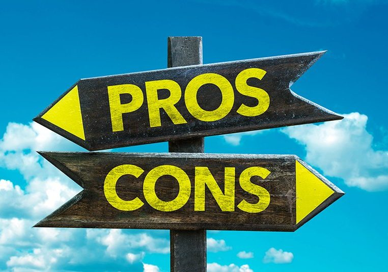 Pros Cons signpost with sky background